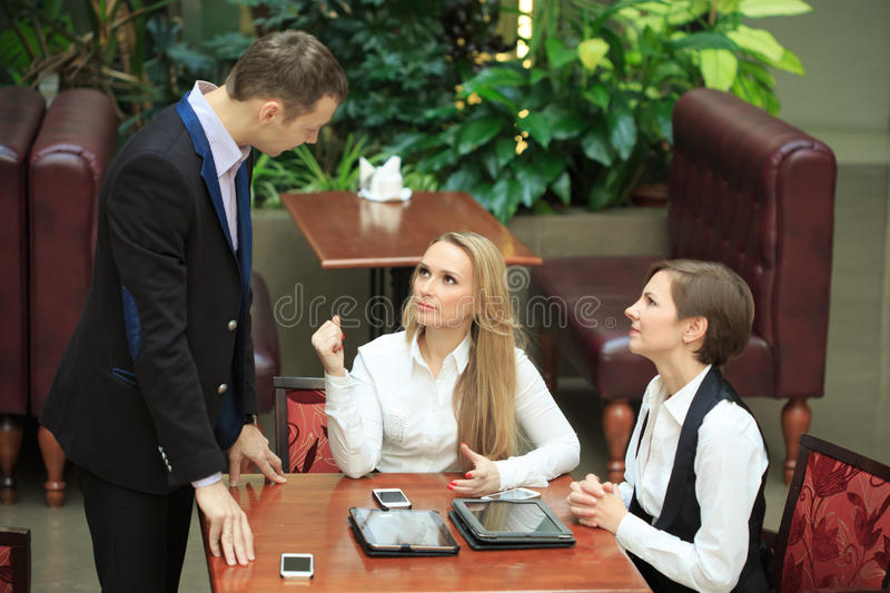 Businessmen sitting in cafe for a laptop. two girls royalty free stock photography