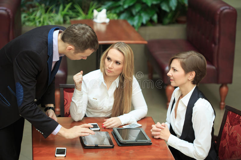Businessmen sitting in cafe for a laptop. two girls stock photo