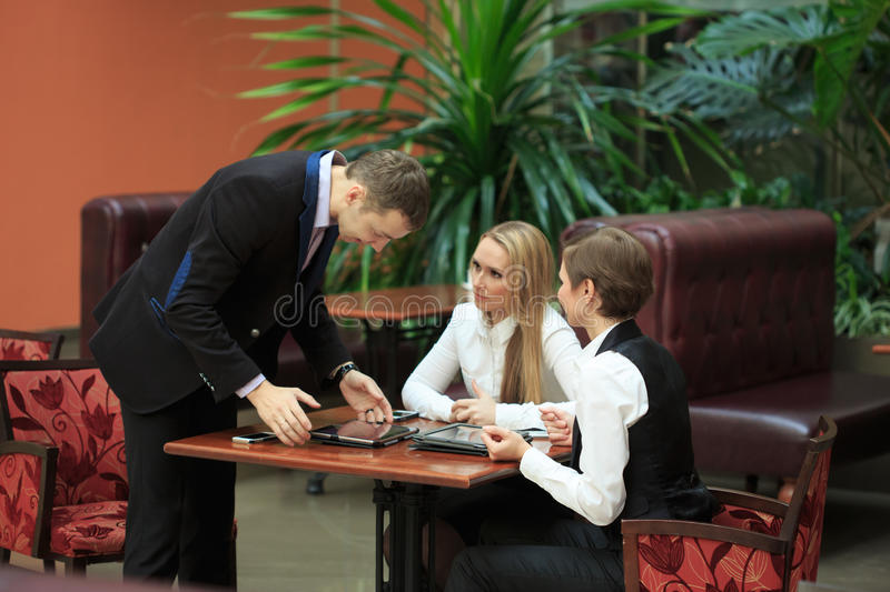 Businessmen sitting in cafe for a laptop. two girls stock photography