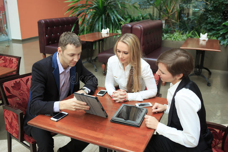 Businessmen sitting in cafe for a laptop. two girls royalty free stock image