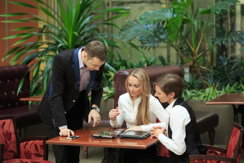 Businessmen sitting in cafe for a laptop. two girls stock photos