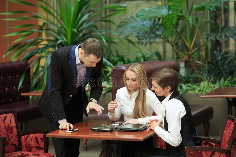 Businessmen sitting in cafe for a laptop. two girls stock image