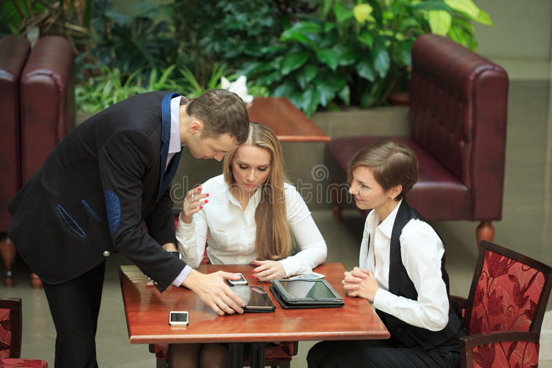 Businessmen sitting in cafe for a laptop. two girls royalty free stock images