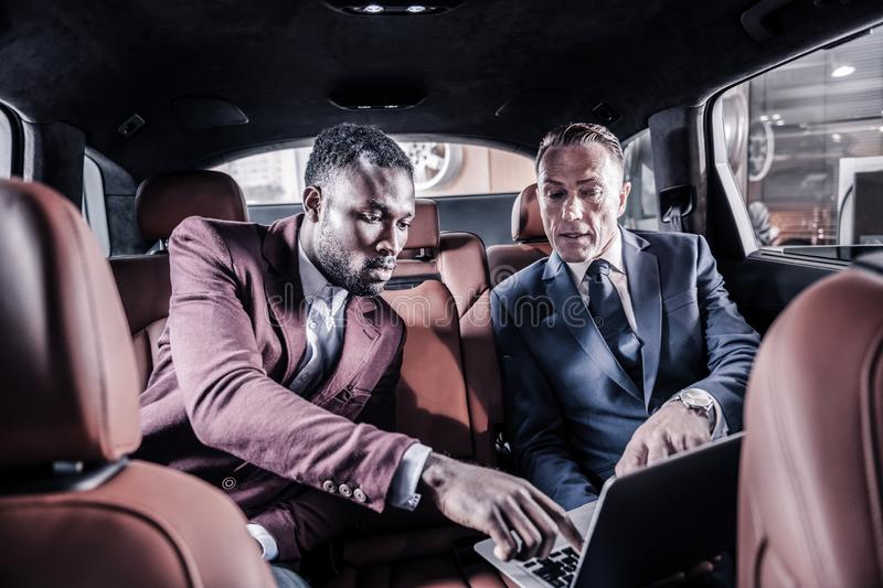 Businessmen sitting in car standing in car dealers watching video about it. Watching video. Two businessmen sitting in car standing in car dealers watching video royalty free stock photos