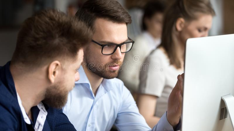 Businessmen sitting together in coworking with other business people stock photo