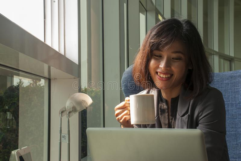 Businessmen are smiling and drinking coffee. A business woman smiled after watching the work on a laptop and lifting the coffee to drink stock photos