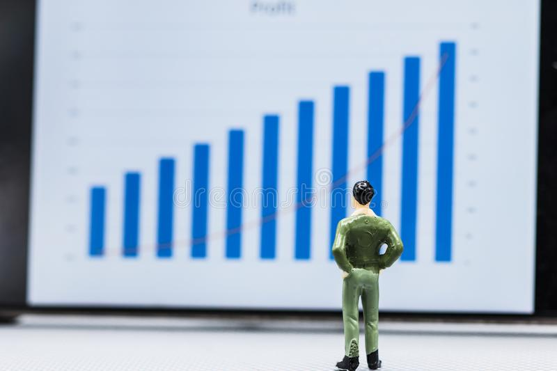 Businessmen stand and look at the graph Marketing Growth display. Miniature people small figures businessmen stand and look at the graph Marketing Growth display stock photo