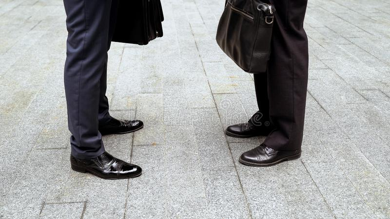 Businessmen standing face to face, closeup on feet in leather shoes, formalwear royalty free stock photography