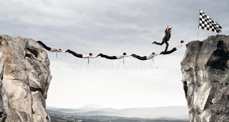 Businessmen support bridge to get to the flag. Achievement business goal concept. Businessmen working together to form a bridge between two mountains to get to royalty free stock photo