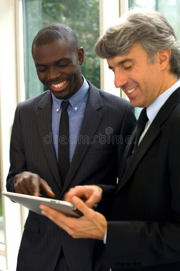 Businessmen with tablet. In office stock images