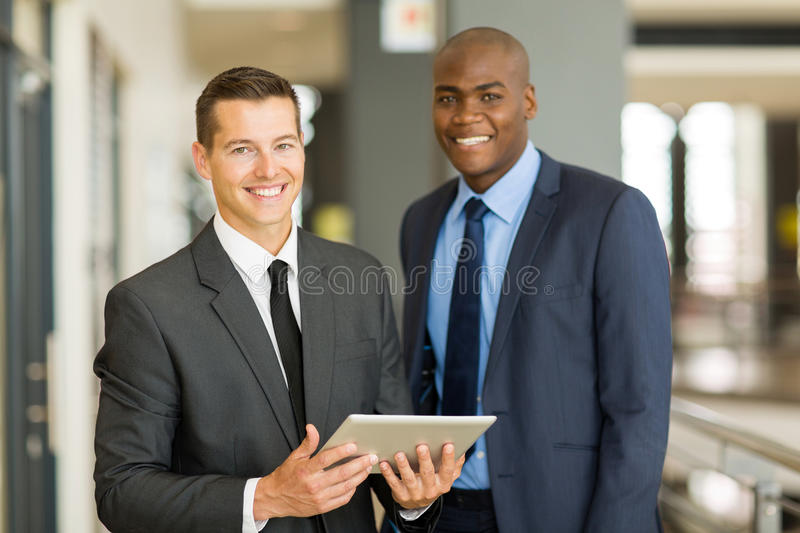 Businessmen tablet pc. Two handsome businessmen using tablet pc in modern office royalty free stock photo