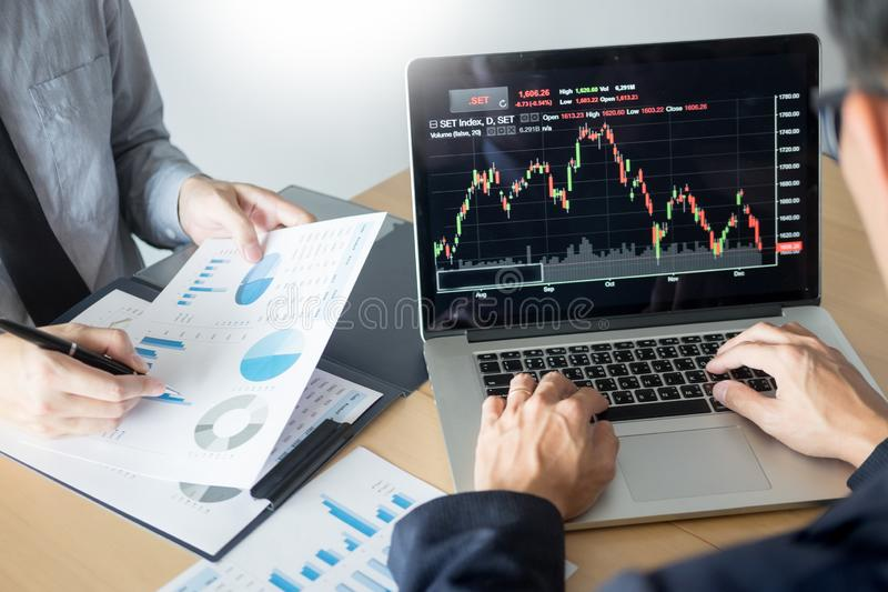 Businessmen talking about stock market invest trading online analysis discussing financial graph for investment purposes. Discussion in traders office stock photo