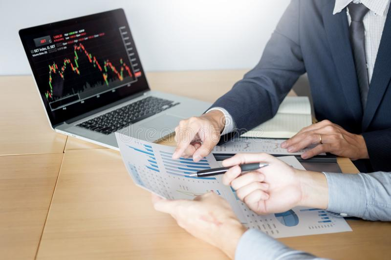 Businessmen talking about stock market invest trading online analysis discussing financial graph for investment purposes. Discussion in traders office stock photography
