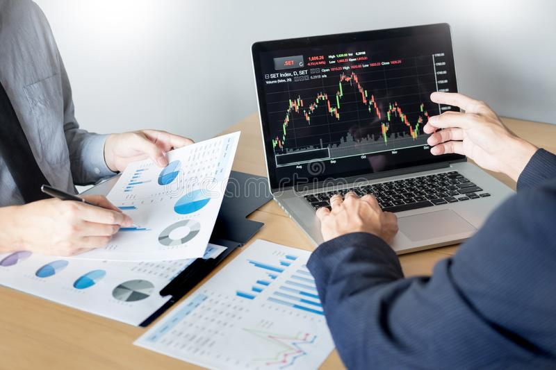 Businessmen talking about stock market invest trading online analysis discussing financial graph for investment purposes. Discussion in traders office stock image