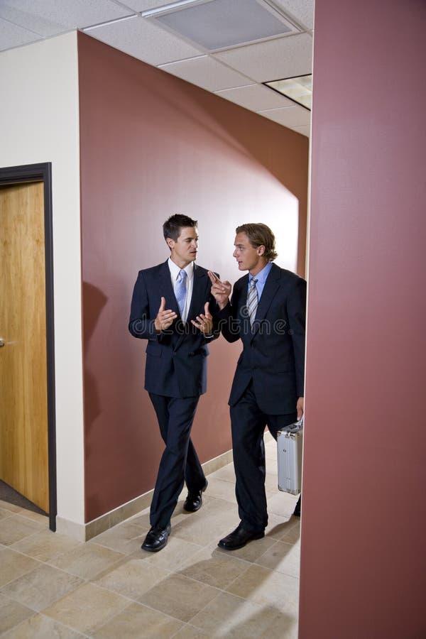 Businessmen talking and walking down corridor stock photos