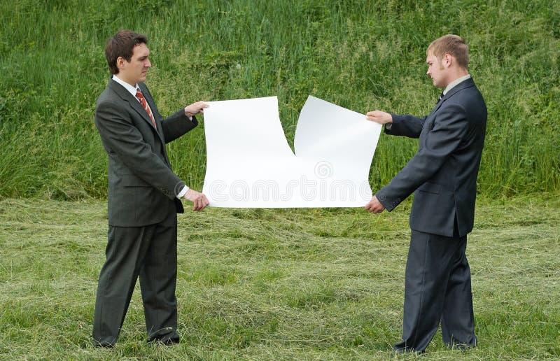 Businessmen tearing sheet of paper