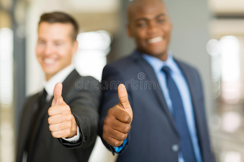 Businessmen thumbs up. Two businessmen giving thumbs up royalty free stock photography