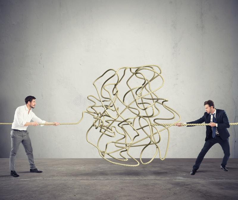 Businessmen try to solve a tangled rope. Concept of partnership stock image