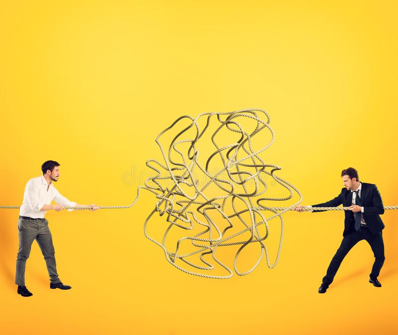 Businessmen try to solve a tangled rope. Concept of partnership royalty free stock photography