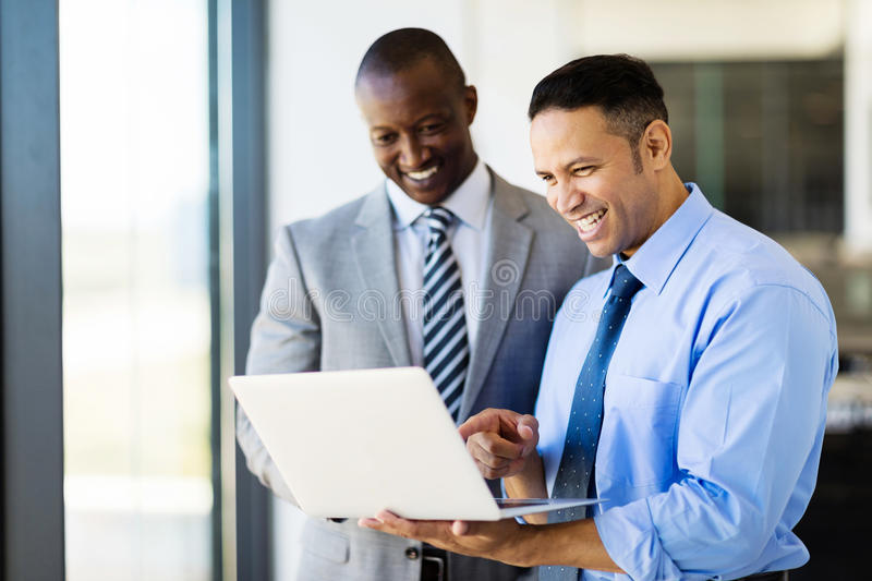 Businessmen using laptop. Two businessman using laptop in modern office royalty free stock photo