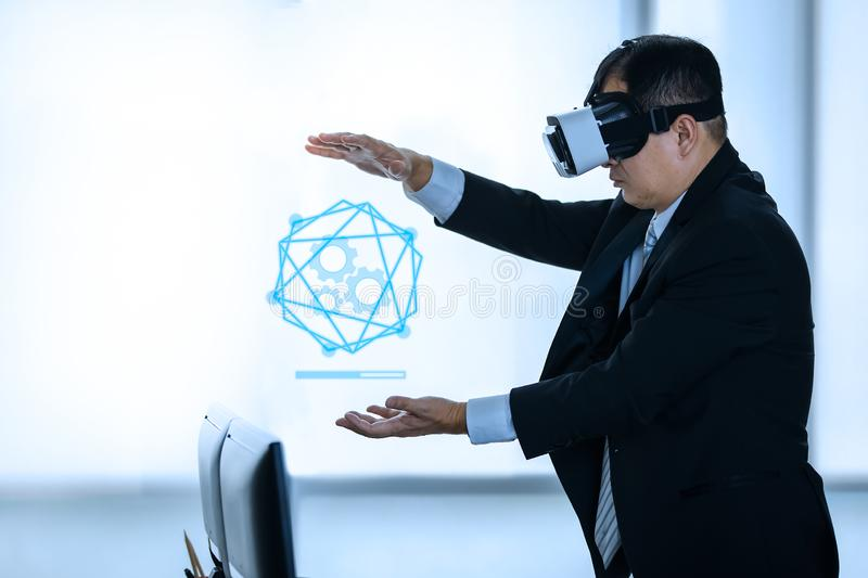 Businessmen viewing the contents of VR device. Middle-aged businessmen are standing and viewing the contents of the virtual reality device, which is a technology stock image