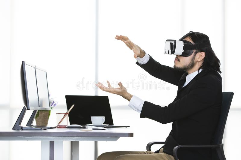 Businessmen viewing the contents of VR device. Young businessmen standing and viewing the contents of the virtual reality device, which is a technology of the stock photo