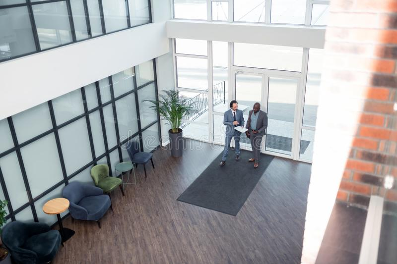 Businessmen walking in business center while having the meeting stock photos