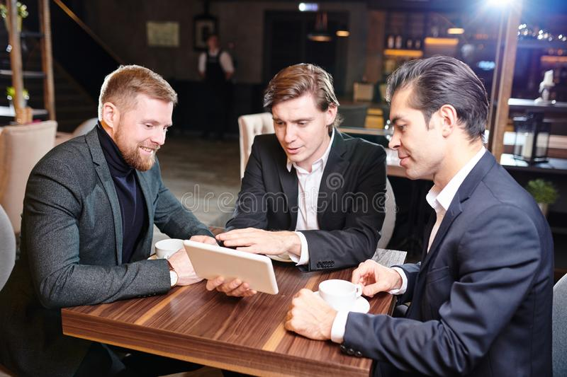Businessmen watching presentation at coffee break royalty free stock photography