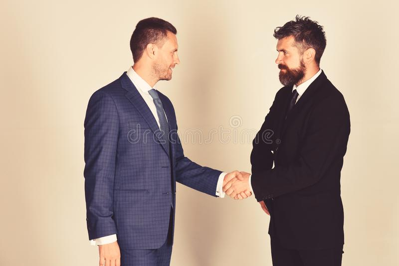 Businessmen wear smart suits and ties. Business agreement and compromise. Concept. Men with beard and calm faces make a deal. CEOs shake hands for partnership royalty free stock photography