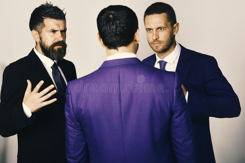 Businessmen wear smart suits and ties. Executives trying to find compromise on light grey background. Men with beard and convictive faces discuss leadership stock image