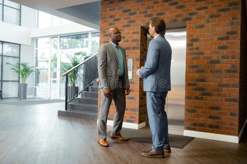 Businessmen wearing suits waiting for elevator in business center stock photography
