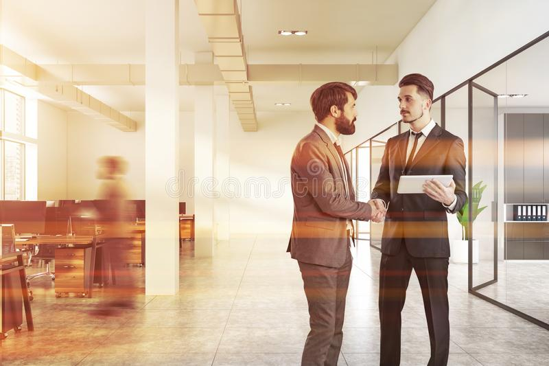 Businessmen in white office hall stock images