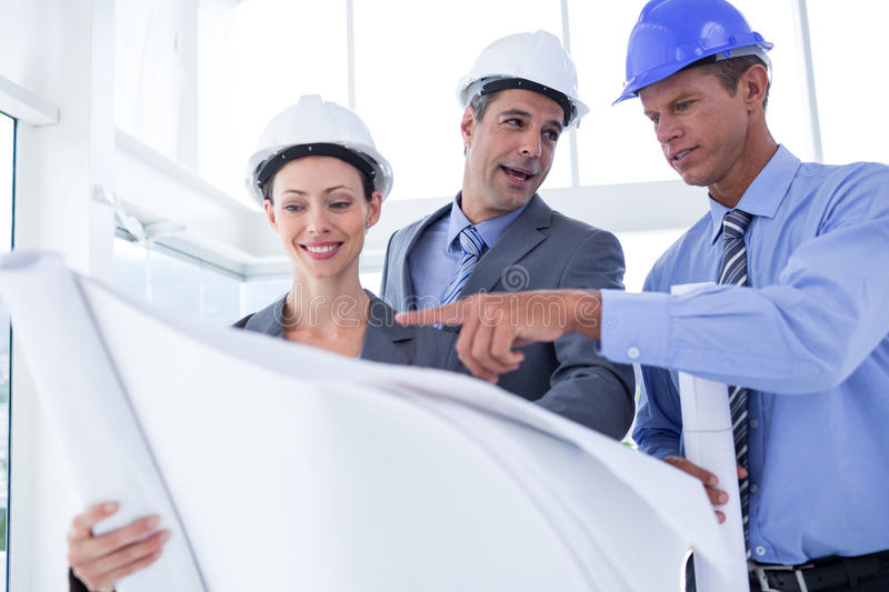 Businessmen and a woman with hard hats and holding blueprint stock photo
