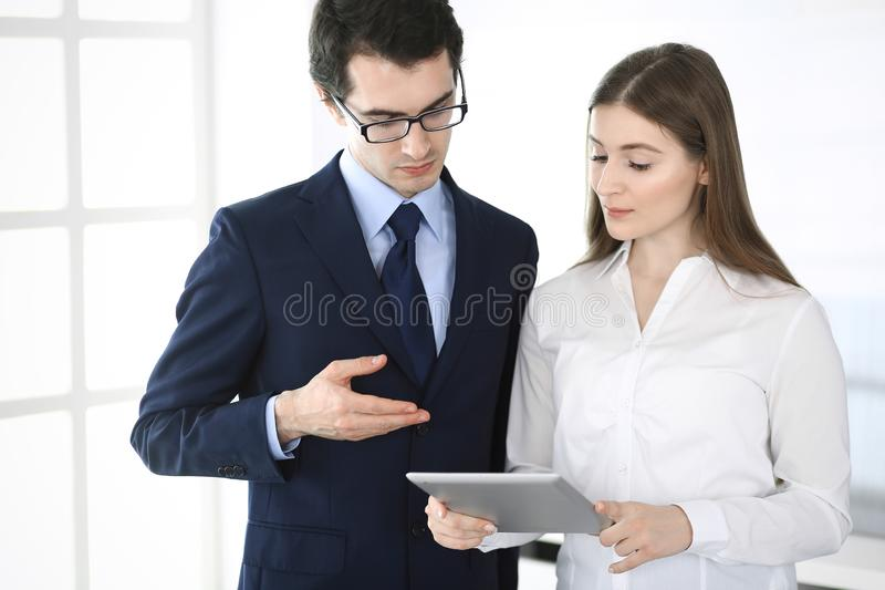 Businessmen and woman using tablet computer in modern office. Colleagues or company managers at workplace. Partners stock photography