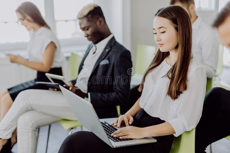 Businessmen and women in conference room on presentation of new product using devices stock photography