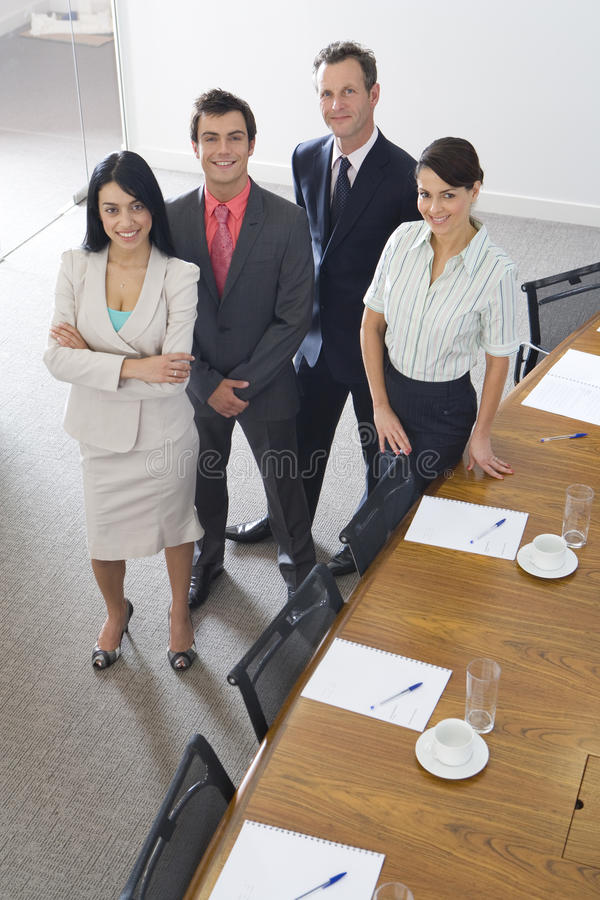 Businessmen and women by conference room table, smiling, portrait, elevated view royalty free stock photo