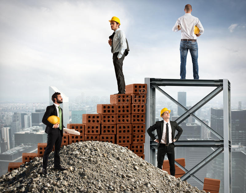 Businessmen work together to build a building. In the city royalty free stock photo
