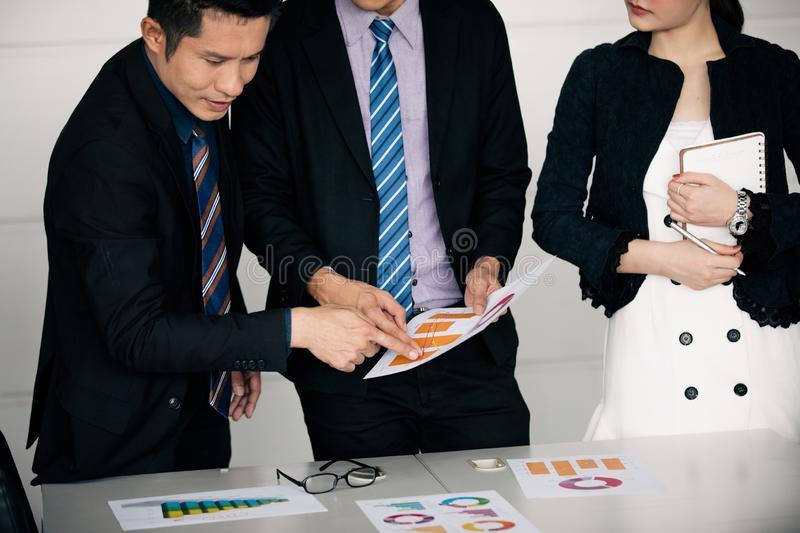 Businessmen working and point on graph financial diagram and analysis documents on office table stock photography