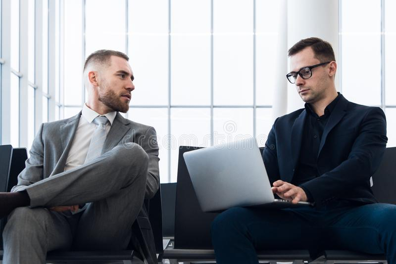 Businessmen working together on laptop in airport lounge stock photography