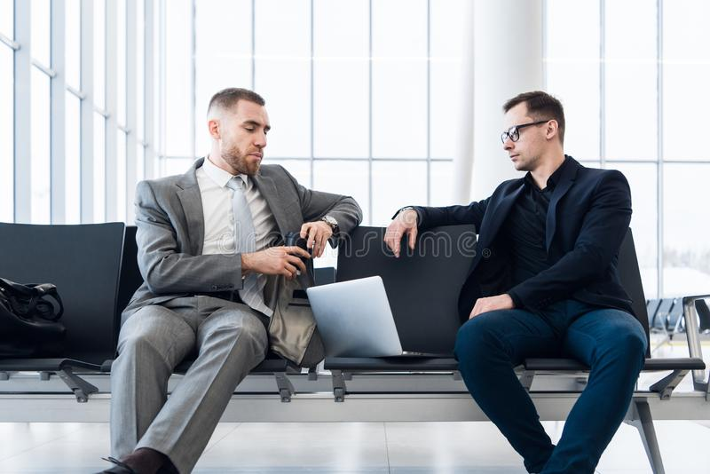 Businessmen working together on laptop in airport lounge royalty free stock image