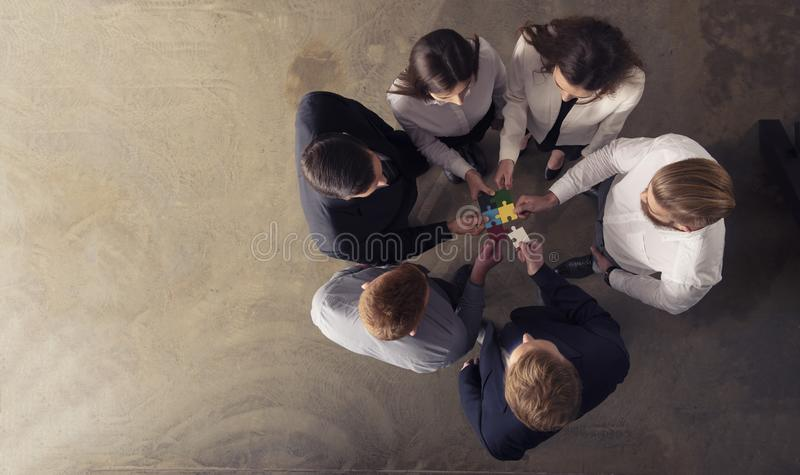 Teamwork of partners. Concept of integration and startup with puzzle pieces. Businessmen working together to build a colored puzzle. Concept of teamwork royalty free stock image