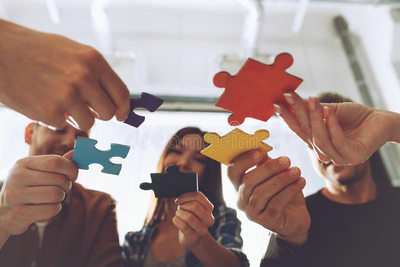 Teamwork of partners. Concept of integration and startup with puzzle pieces. Businessmen working together to build a puzzle. Concept of teamwork, partnership stock photography