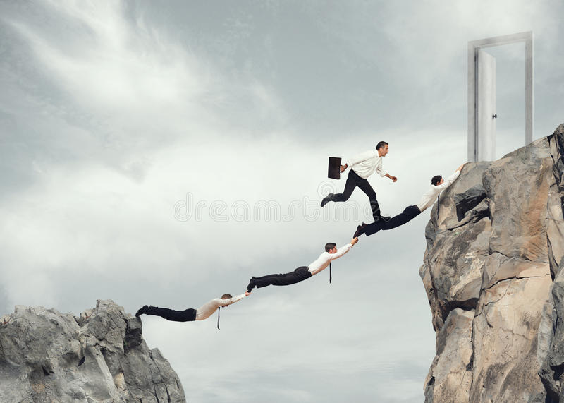 Businessmen working together to reach a door. Businessmen working together to form a bridge between two mountains to reach a door. concept of ambition in stock photo