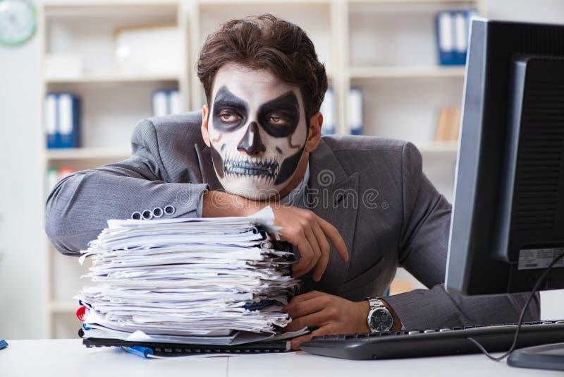 Businessmsn при страшный лицевой щиток гермошлема работая в офисе стоковое фото
