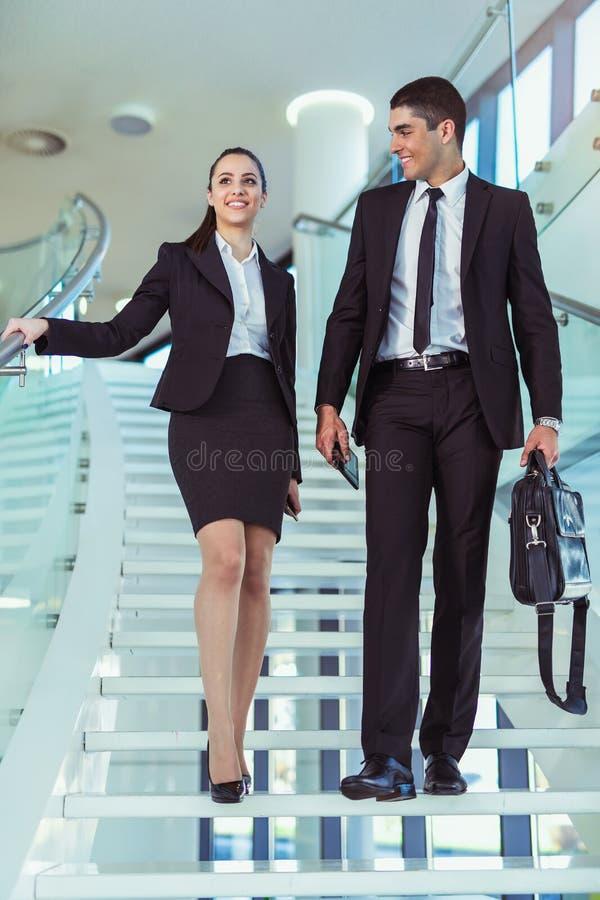 Businesspeople δύο που μιλά καθώς μπαίνουν μέσα το γραφείο στοκ εικόνες