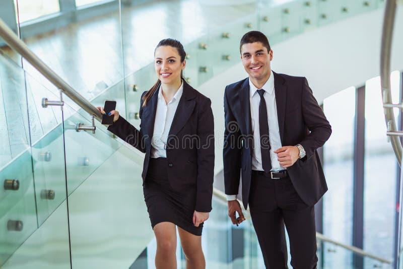 Businesspeople που μιλά καθώς μπαίνουν μέσα το γραφείο στοκ εικόνες