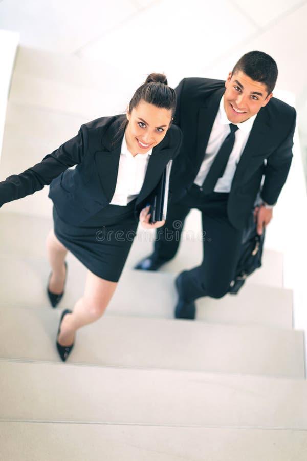 Businesspeople που μιλά καθώς μπαίνουν μέσα το γραφείο στοκ φωτογραφία
