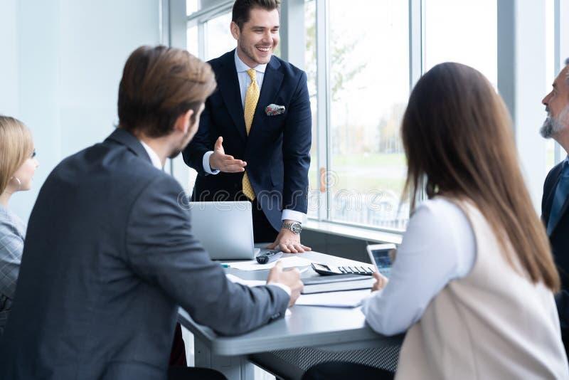 Businesspeople που συζητά μαζί στη αίθουσα συνδιαλέξεων κατά τη διάρκεια της συνεδρίασης στο γραφείο στοκ φωτογραφία
