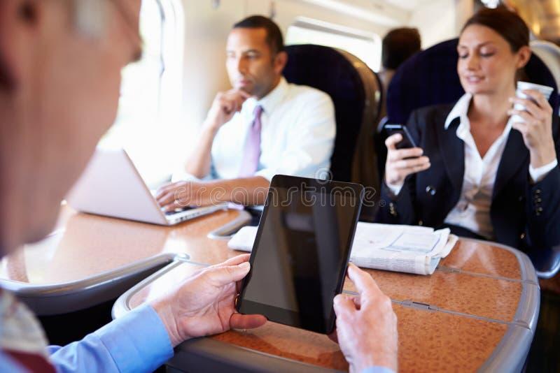 Businesspeople στο τραίνο που χρησιμοποιεί τις ψηφιακές συσκευές στοκ εικόνα