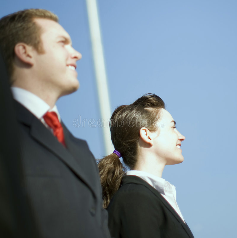 Businesspeople. Profile view of businessman and businesswoman standing in formal wear royalty free stock images